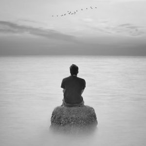 man sitting between water
